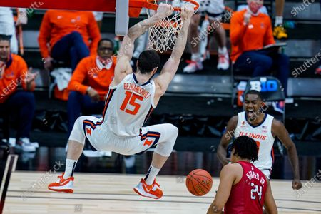Illinois guard Da'Monte Williams, right rear, celebrates as Giorgi Bezhanishvili follows through on a dunk over Rutgers' Ron Harper Jr. during the second half of an NCAA college basketball game at the Big Ten Conference men's tournament in Indianapolis
