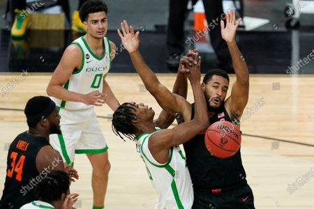 Oregon State's Maurice Calloo, right, fouls Oregon's Eric Williams Jr. (50) during the first half of an NCAA college basketball game in the semifinal round of the Pac-12 men's tournament, in Las Vegas