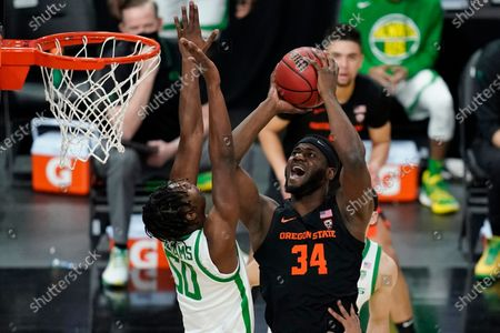 Oregon State's Rodrigue Andela (34) shoots over Oregon's Eric Williams Jr. (50) during the first half of an NCAA college basketball game in the semifinal round of the Pac-12 men's tournament, in Las Vegas