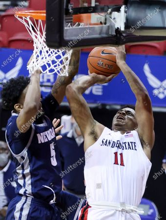 San Diego State forward Matt Mitchell (11) shoots as Nevada forward Warren Washington (5) defends during the first half of an NCAA college basketball game in the semifinal round of the Mountain West Conference men's tournament, in Las Vegas