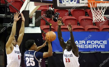 Nevada guard Grant Sherfield (25) passes as San Diego State forward Matt Mitchell (11) and forward Aguek Arop (33) defend during the first half of an NCAA college basketball game in the semifinal round of the Mountain West Conference men's tournament, in Las Vegas