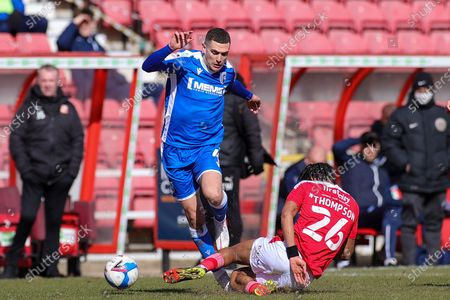 Dominic Thompson (26) of Swindon Town slides in and tackles Stuart O'Keefe (4) of Gillingham during the EFL Sky Bet League 1 match between Swindon Town and Gillingham at the County Ground, Swindon