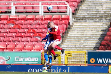 Paul Caddis (2) of Swindon Town and Stuart O'Keefe (4) of Gillingham clash in the air during the EFL Sky Bet League 1 match between Swindon Town and Gillingham at the County Ground, Swindon