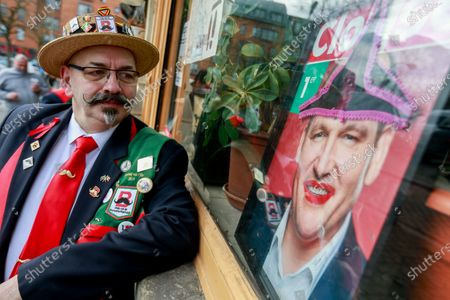 A customer looks at a poster of Brussels mayor Philippe Close while a bar owner decides to open its doors to mark one year of the first confinement in 'Les Marolles' in Brussels, Belgium, 13 March 2021. Workers of the cultural sector took part in various actions in different cultural places of the country to denounce the lack of financial support and call for solutions to the impact of the coronavirus crisis on culture professionals and the sector as a whole one year after the Covid-19 pandemic lockdowns started.