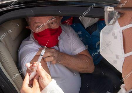 Former Brazilian President Luiz Inacio Lula da Silva eyes the syringe that will deliver his shot of the Sinovac COVID-19 vaccine at a drive-thru site in Sao Bernardo do Campo, Sao Paulo state, Brazil