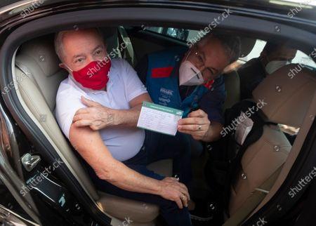 Former Brazilian President Luiz Inacio Lula da Silva, left, shows his vaccination document after getting a shot of the the Sinovac COVID-19 vaccine at a drive-thru site in Sao Bernardo do Campo, Sao Paulo state, Brazil