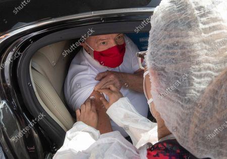 Health worker gives a shot of he Sinovac COVID-19 vaccine to former Brazilian President Luiz Inacio Lula da Silva at a drive-thru site in Sao Bernardo do Campo, Sao Paulo state, Brazil