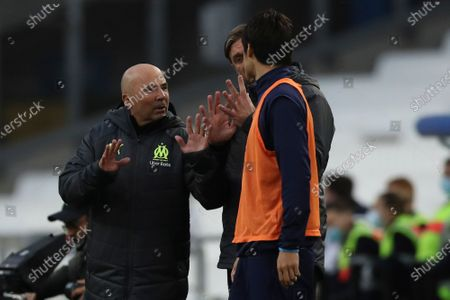 Marseille's coach Jorge Sampaoli, left, talks to Marseille's Hiroki Sakai during the French League One soccer match between Marseille and Brest at the Stade Veledrome stadium in Marseille, France