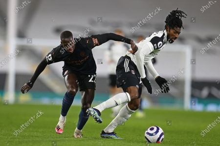 Manchester City's Benjamin Mendy, left, challenges for the ball with Fulham's Andre-Frank Zambo Anguissa during an English Premier League soccer match between Fulham and Manchester City at the Craven Cottage stadium in London, England