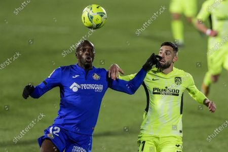 Getafe's Allan Nyom, left, duels for the ball with Atletico Madrid's Yannick Carrasco during the Spanish La Liga soccer match between Getafe and Atletico Madrid at the Alfonso Perez stadium in Getafe, Spain