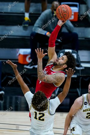 Ohio State guard Duane Washington Jr. (4) shoots over Michigan guard Mike Smith (12) in the first half of an NCAA college basketball game at the Big Ten Conference tournament in Indianapolis