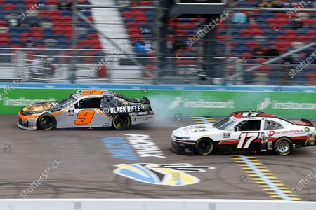 Smoke comes from the rear of Noah Gragson's race car (9) as he is passes JJ Yeley (17) during a NASCAR Xfinity Series auto race at Phoenix Raceway, in Avondale, Ariz