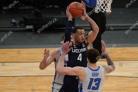 Creighton's Christian Bishop (13) defends Connecticut's Tyrese Martin (4) during the first half of an NCAA college basketball game in the semifinals in the Big East men's tournament, in New York