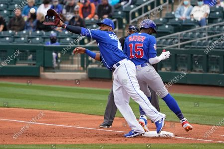 Kansas City Royals' first baseman Carlos Santana, left, is pulled off the bag as he reaches for the ball on a pick-off attempt of Chicago Cubs' Cameron Maybin (15) in the second inning of a spring training baseball game, in Surprise, Ariz