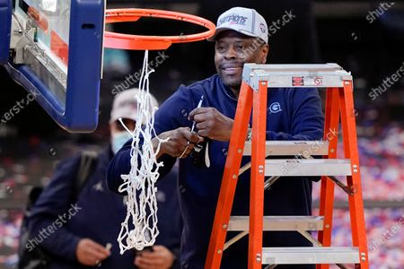Georgetown head coach Patrick Ewing cuts down the net after an NCAA college basketball game against Creighton in the championship of the Big East Conference tournament, in New York