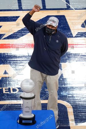 Georgetown head coach Patrick Ewing gestures towards fans while standing next to the tournament trophy after an NCAA college basketball game in the championship of the Big East Conference tournament, in New York