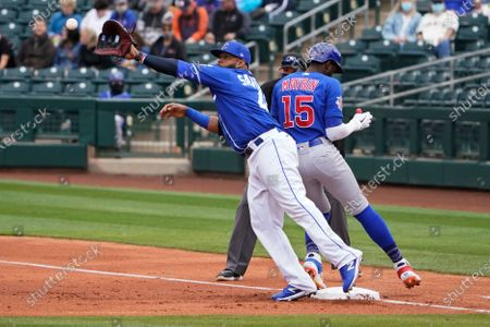 Kansas City Royals first baseman Carlos Santana, left, is pulled off the bag as he reaches for the ball on a pickoff attempt of Chicago Cubs' Cameron Maybin (15) during the second inning of a spring training baseball game, in Surprise, Ariz