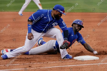 Kansas City Royals first baseman Carlos Santana, left, tags out Chicago Cubs' Cameron Maybin on a pickoff in the fourth inning of a spring training baseball game, in Surprise, Ariz