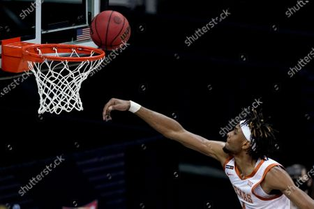 Stock Photo of Texas's Greg Brown puts up a shot during the first half of an NCAA college basketball game against Oklahoma State for the Big 12 tournament championship in Kansas City, Mo