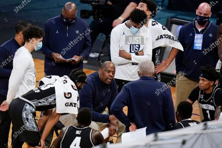Georgetown coach Patrick Ewing, lower center, talks to the team during the first half of an NCAA college basketball game against Creighton for the championship of the Big East men's tournament, in New York