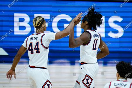 Illinois guard Adam Miller (44) and guard Ayo Dosunmu (11) celebrate in the first half of an NCAA college basketball game against Iowa at the Big Ten Conference tournament in Indianapolis