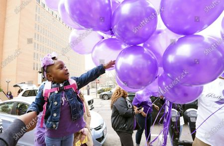 Little two year old Ryan Baldwin reaches for a balloon prior to a End Domestic Violence rally in Clayton, Missouri on Saturday, March 13, 2021. The rally was being held in honor of Roseann McCulley and her children, Kayden Johnson, and Kaylee Brooks. Police say Bob McCulley III is responsible for killing his wife and her two children then taking his own life on March 4, 2021.The woman was 34-years-old and the two children were 13 and six years old.