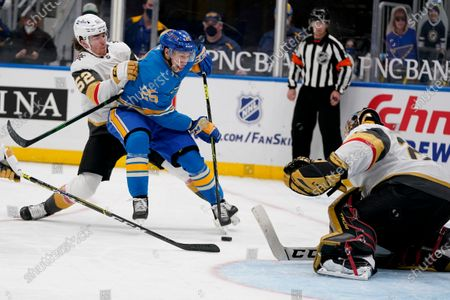 St. Louis Blues' Jordan Kyrou (25) tries to get off a shot as Vegas Golden Knights goaltender Marc-Andre Fleury and Dylan Coghlan (52) defend during the second period of an NHL hockey game, in St. Louis