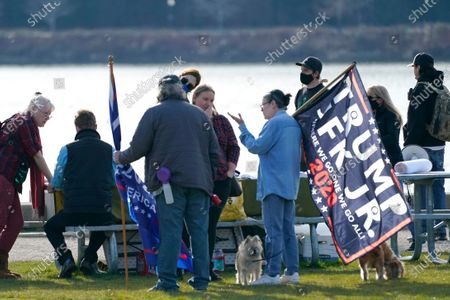 """A person holds a flag promoting former President Donald Trump and John F. Kennedy Jr. - who died in a plane crash in 1999 - as potential running mates in the 2020 presidential election, during a rally at a park in Olympia, Wash. The flag also has references to """"Q"""" and QAnon, a baseless and wide-ranging conspiracy theory spread largely through the internet that is based on cryptic postings by the anonymous """"Q,"""" purportedly a government insider"""
