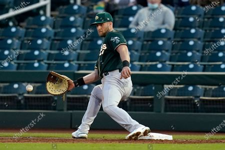 Oakland Athletics first baseman Seth Brown reaches to catch the ball to get Cincinnati Reds' Eugenio Suarez out at first base during the first inning of a spring training baseball game, in Goodyear, Ariz