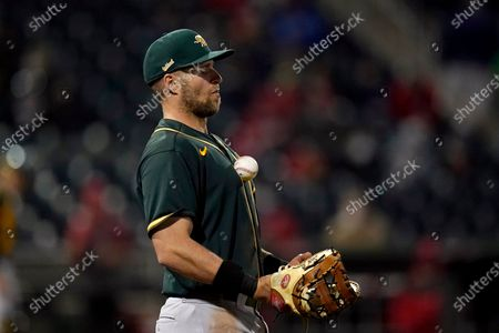 Oakland Athletics first baseman Seth Brown bounces a ball off his chest during the third inning of a spring training baseball game against the Cincinnati Reds, in Goodyear, Ariz