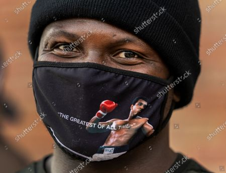 """Photographer Michael Omeka wears a face mask with a Muhammad Ali image as he participates in the rally """"Love Our Communities: Build Collective Power"""" to raise awareness of anti-Asian violence outside the Japanese American National Museum in Little Tokyo in Los Angeles . Los Angeles County officials are stepping up their efforts to battle hate crimes against Asian Americans. The """"LA vs. Hate"""" initiative encourages people to call 211 if they are victims or witness an incident of hate"""
