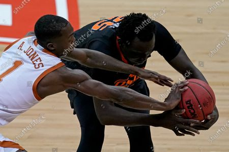Texas's Andrew Jones (1) and Oklahoma State's Bernard Kouma battle for a loose ball during the first half of an NCAA college basketball game for the Big 12 tournament championship in Kansas City, Mo