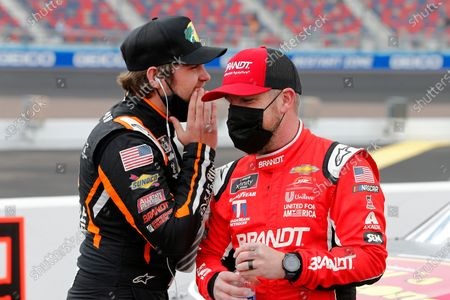 Noah Gragson, left, tells a joke to Justin Allgaier prior to a NASCAR Xfinity Series auto race at Phoenix Raceway, in Avondale, Ariz. Gibbs finished second in the race