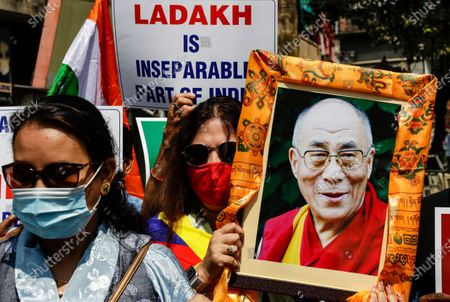 Stock Photo of Indians and exile Tibetans, one holding a portrait of their spiritual leader Dalai Lama, participate in a rally to highlight alleged Chinese atrocities in Tibet, in Kolkata, India