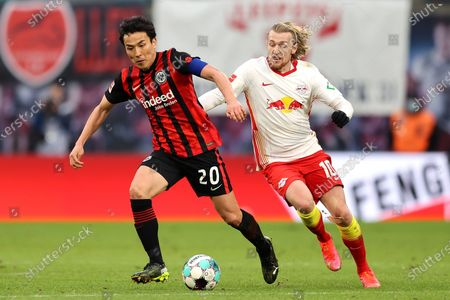 Makoto Hasebe of Eintracht Frankfurt (L) battles for possession with Emil Forsberg of RB Leipzig  during the Bundesliga match between RB Leipzig and Eintracht Frankfurt at Red Bull Arena in Leipzig, Germany, 14 March 2021.