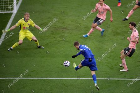 Leicester's Jamie Vardy, foreground, takes a shot that Sheffield United's Ethan Ampadu, background deflects into his own goal during the English Premier League soccer match between Leicester City and Sheffield United at the King Power Stadium in Leicester, England