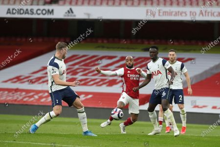 Alexandre Lacazette (C) of Arsenal in action against Davinson Sanchez (2-R) of Tottenham during the English Premier League soccer match between Arsenal FC and Tottenham Hotspur in London, Britain, 14 March 2021.