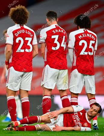 Arsenal's Cedric Soares (bottom) lies behind the wall during the English Premier League soccer match between Arsenal FC and Tottenham Hotspur in London, Britain, 14 March 2021.