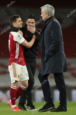 Arsenal manager Mikel Arteta (C) celebrates with Cedric Soares (L) as Tottenham manager Jose Mourinho (R) leaves the pitch after the English Premier League soccer match between Arsenal FC and Tottenham Hotspur in London, Britain, 14 March 2021.