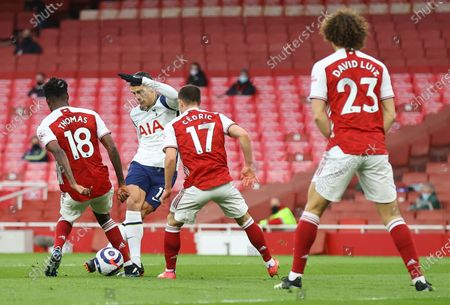 Tottenham's Erik Lamela (C) scores the opening goal with a rabona past Arsenal players Thomas Partey (L) and Cedric Soares (R) during the English Premier League soccer match between Arsenal FC and Tottenham Hotspur in London, Britain, 14 March 2021.