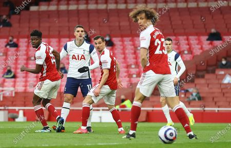 Tottenham's Erik Lamela (C) watches the ball as he scores the opening goal with a rabona past Arsenal players Thomas Partey (L) and Cedric Soares (R) and David Luiz (foreground) during the English Premier League soccer match between Arsenal FC and Tottenham Hotspur in London, Britain, 14 March 2021.
