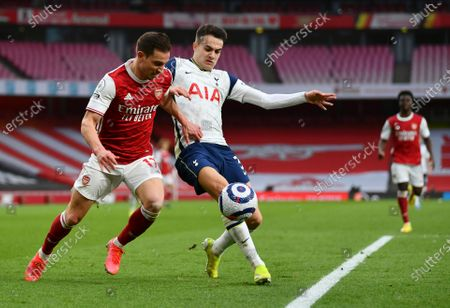 Arsenal's Cedric Soares, left, and Tottenham's Sergio Reguilon challenge for the ball during the English Premier League soccer match between Arsenal and Tottenham Hotspur at the Emirates stadium in London, England