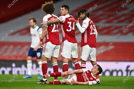 Cedric Soares lies on the floor beneath the defensive wall during a free kick at goal during the English Premier League soccer match between Arsenal and Tottenham Hotspur at the Emirates stadium in London, England