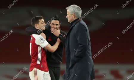 Arsenal's manager Mikel Arteta greets Arsenal's Cedric Soares as Tottenham's manager Jose Mourinho passes by after the English Premier League soccer match between Arsenal and Tottenham Hotspur at the Emirates stadium in London, England