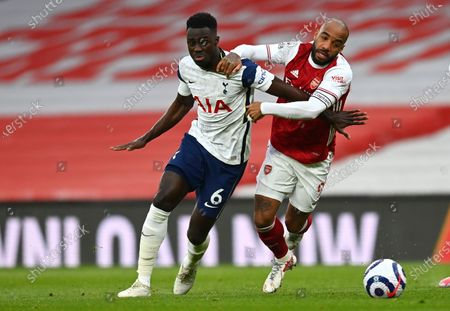 Tottenham's Davinson Sanchez, left, and Arsenal's Alexandre Lacazette challenge for the ball during the English Premier League soccer match between Arsenal and Tottenham Hotspur at the Emirates stadium in London, England