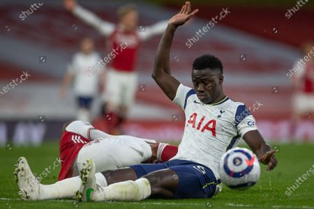 Davinson Sanchez of Tottenham Hotspur holds his hand up in denial after fouling Alexandre Lacazette of Arsenal