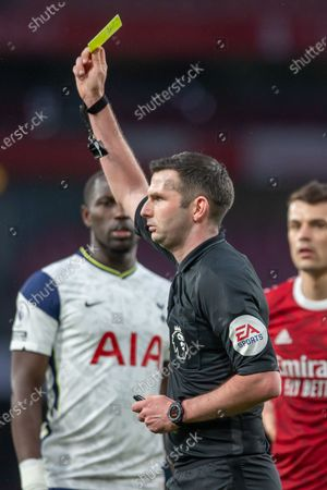 Referee Michael Oliver gives yellow card to Davinson Sanchez of Tottenham Hotspur