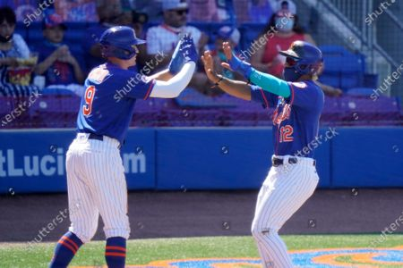 New York Mets' Brandon Nimmo (9) and Francisco Lindor (12) high-five after scoring on a single hit by Pete Alonso during the fifth inning of a spring training baseball game against the St. Louis Cardinals, in Port St. Lucie, Fla