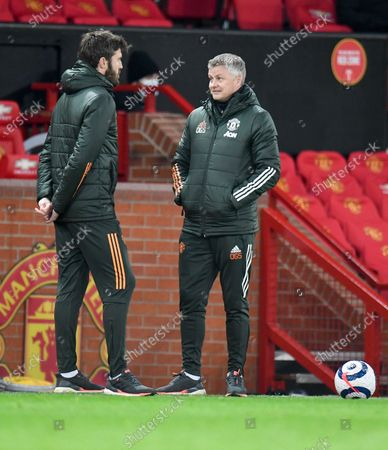 Manchester United's manager Ole Gunnar Solskjaer, right, talks with Michael Carrick during the English Premier League soccer match between Manchester United and West Ham United at Old Trafford, Manchester, England