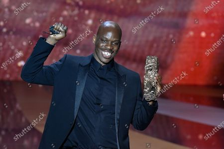 """Stock Picture of French actor Jean-Pascal Zadi poses with his trophy after receiving the Best Male Newcomer award for the movie """"Tout simplement noir"""" (Simply Black) 46th Cesar Film Awards 2021 ceremony at l'Olympia."""
